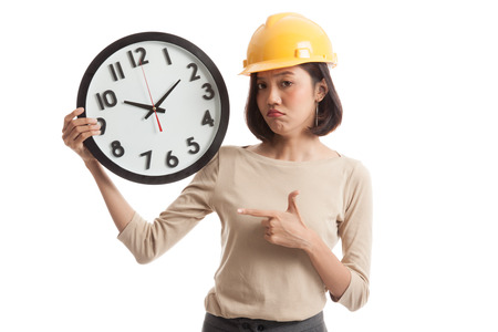 sulk: Asian engineer woman in bad mood with a clock  isolated on white background Stock Photo