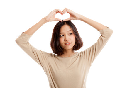 alzando la mano: Young Asian woman gesturing heart hand sign  isolated on white background