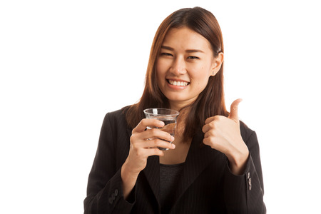 woman thumbs up: Young Asian woman thumbs up with a glass of drinking water  isolated on white background. Stock Photo