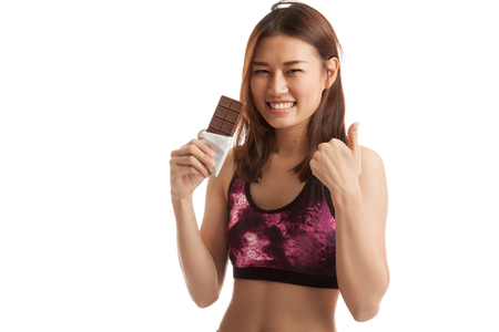 lose up: Beautiful healthy Asian girl thumbs up with chocolate  isolated on white background. Stock Photo