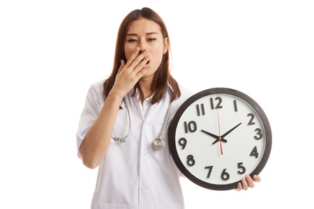 Young Asian female doctor yawn with a clock  isolated on white background. Stock Photo