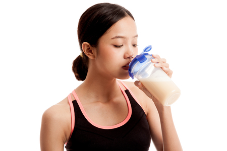 whey: Beautiful Asian healthy girl drinking whey protein  isolated on white background .