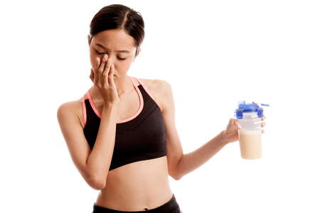 Beautiful Asian healthy girl hate whey protein  isolated on white background .
