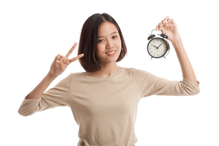 victory sign: Young Asian business woman show victory sign with a clock  isolated on white background .