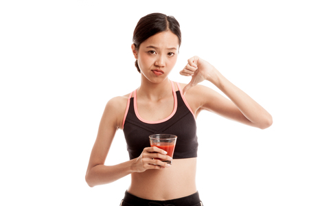 Beautiful healthy Asian girl hate tomato juice thumbs down  isolated on white background .