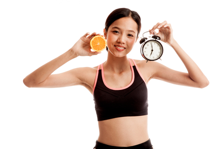 Beautiful Asian healthy girl with orange and clock  isolated on white background .