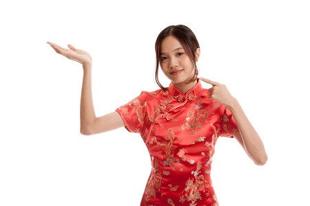 chipao: Asian girl in chinese cheongsam dress point to  blank space on her hand isolated on white background .