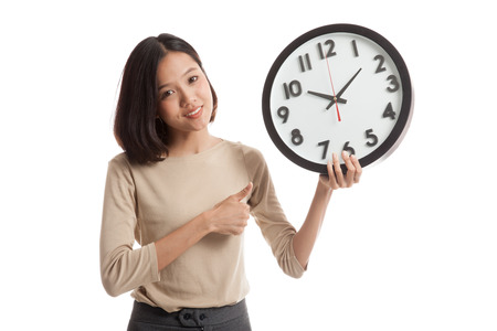 office time: Young Asian business woman thumbs up with a clock  isolated on white background .