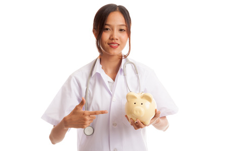 Young Asian female doctor point to a pig bank coin  isolated on white background .