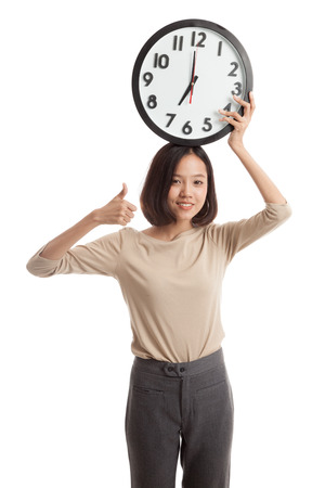 woman thumbs up: Young Asian business woman thumbs up with a clock  isolated on white background .