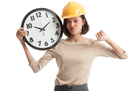 sulk: Asian engineer woman thumbs down with a clock  isolated on white background .