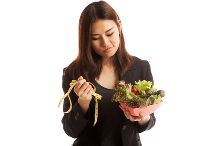 eating salad: Unhappy Asian business woman with measuring tape and salad  isolated on white background. Stock Photo