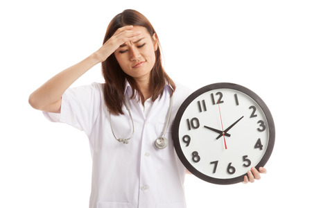 fed up: Young Asian female doctor headache with a clock  isolated on white background.