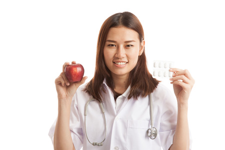 Young Asian female doctor with pills and apple  isolated on white background.