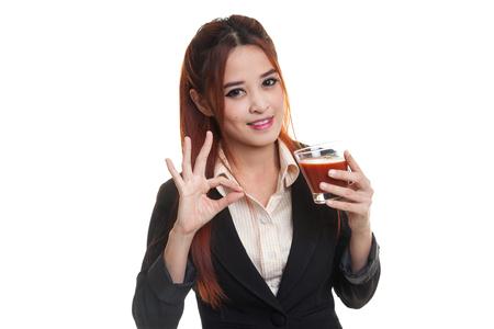 Junge asiatische Geschäftsfrau zeigen OK mit Tomatensaft auf weißem Hintergrund.