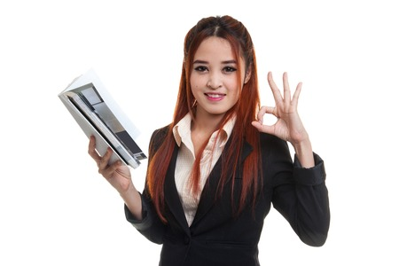 Young Asian business woman show OK with a book  isolated on white background.