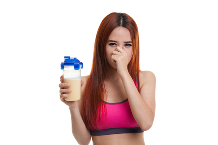 whey: Beautiful Asian healthy girl hate whey protein smell  isolated on white background.