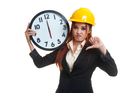 sulk: Asian engineer woman thumbs down with a clock  isolated on white background. Stock Photo