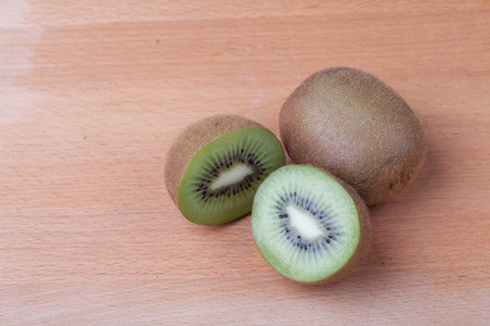 kiwi fruta: Close up of half cut kiwifruit on wooden table Foto de archivo