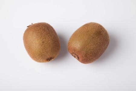 kiwi fruta: Dos kiwis maduros en el fondo blanco Foto de archivo