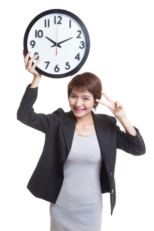 victory sign: Young Asian business woman show victory sign with a clock  isolated on white background.