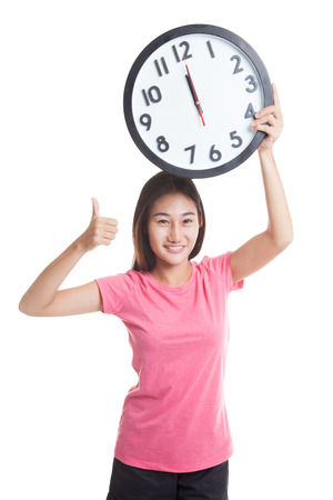 woman thumbs up: Young Asian woman thumbs up with a clock  isolated on white background. Stock Photo
