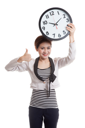 woman thumbs up: Young Asian business woman thumbs up with a clock  isolated on white background.