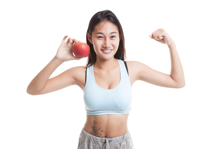 flexing: Beautiful Asian healthy girl  flexing biceps with red apple  isolated on white background.
