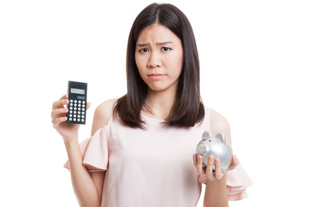 Unhappy Asian business woman with calculator and piggy bank  isolated on white background. Stock Photo