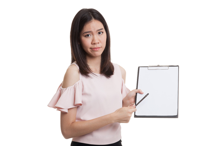 Unhappy Asian business woman point to clipboard with pen  isolated on white background.