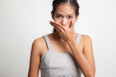 Young Asian woman close her mouth with hand on white background