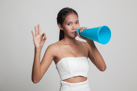 Beautiful young Asian woman show OK  announce with megaphone  on gray background