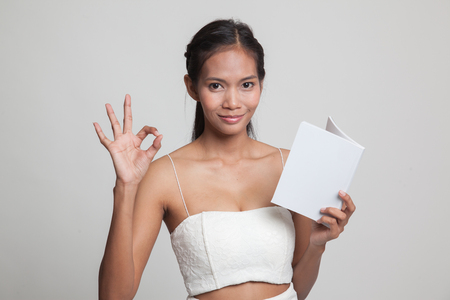 Young Asian woman show OK with a book  on gray background