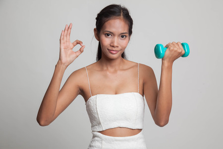signo pesos: Healthy Asian woman show OK with dumbbells  on gray background Foto de archivo