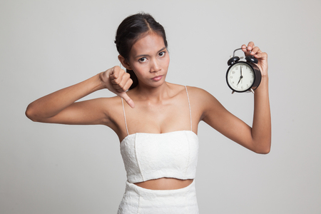Young Asian woman thumbs down with a clock  on gray background