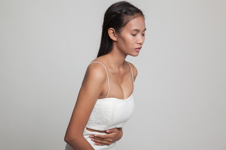 Young Asian woman got stomachache  on gray background Stock Photo