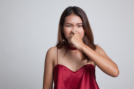 Young Asian woman  holding her nose because of a bad smell on gray background
