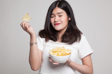 Young Asian woman eat potato chips on gray background Foto de archivo