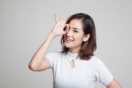 Beautiful young Asian woman show OK sign over her eye on gray background