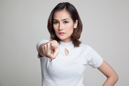 sulk: Young Asian woman angry and point to camera on gray background