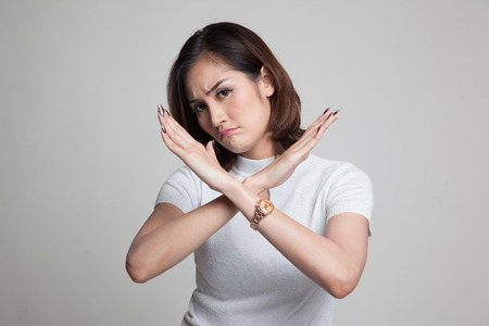 Beautiful young Asian woman say no on gray background
