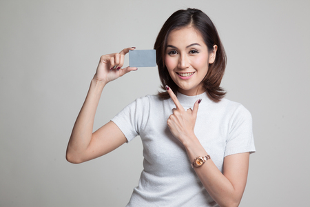 Young Asian woman point to a blank card on gray background Banco de Imagens