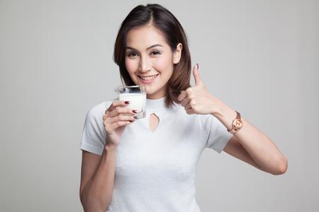 Mulher asiática saudável beber um copo de leite polegares para cima em fundo cinza