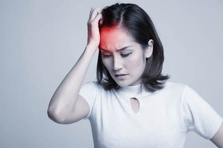 Young Asian woman got sick and  headache on gray background