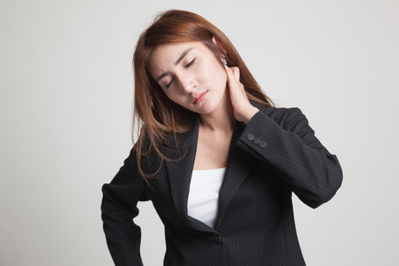 back ache: Young Asian woman got neck pain on gray background Stock Photo