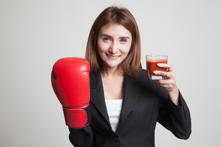 Young Asian woman with tomato juice and boxing glove on gray background
