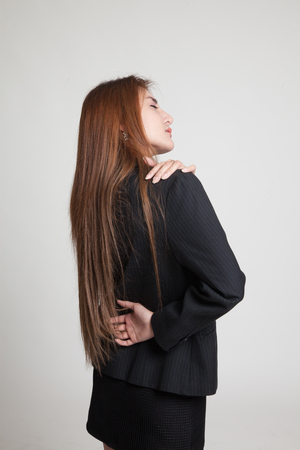 back ache: Young Asian woman got back pain on gray background Stock Photo