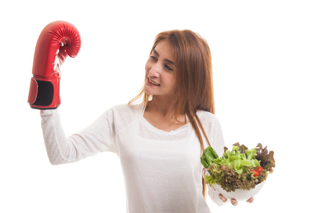 Young Asian woman with boxing glove and salad  isolated on white background