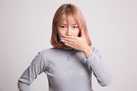 word of mouth: Young Asian woman close her mouth with hand on gray background Stock Photo