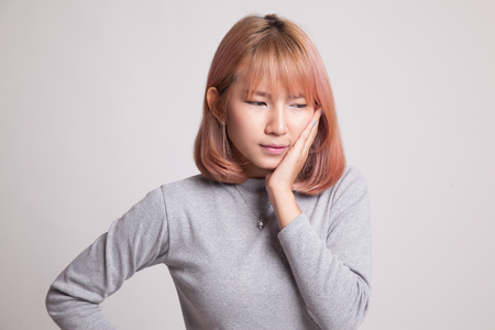 pain: Young Asian woman got toothache on gray background